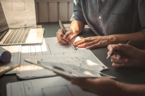Bilde av ingeniører som diskuterer over en arkitekttegning - Byggeteknikk - Ålesund Consult AS